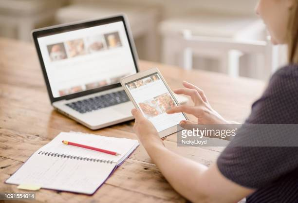 woman viewing her website on a tablet and laptop - the media stock pictures, royalty-free photos & images
