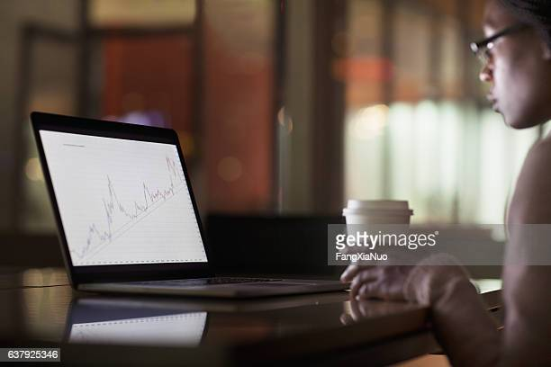 woman viewing laptop screen with graph diagram - reforma assunto imagens e fotografias de stock