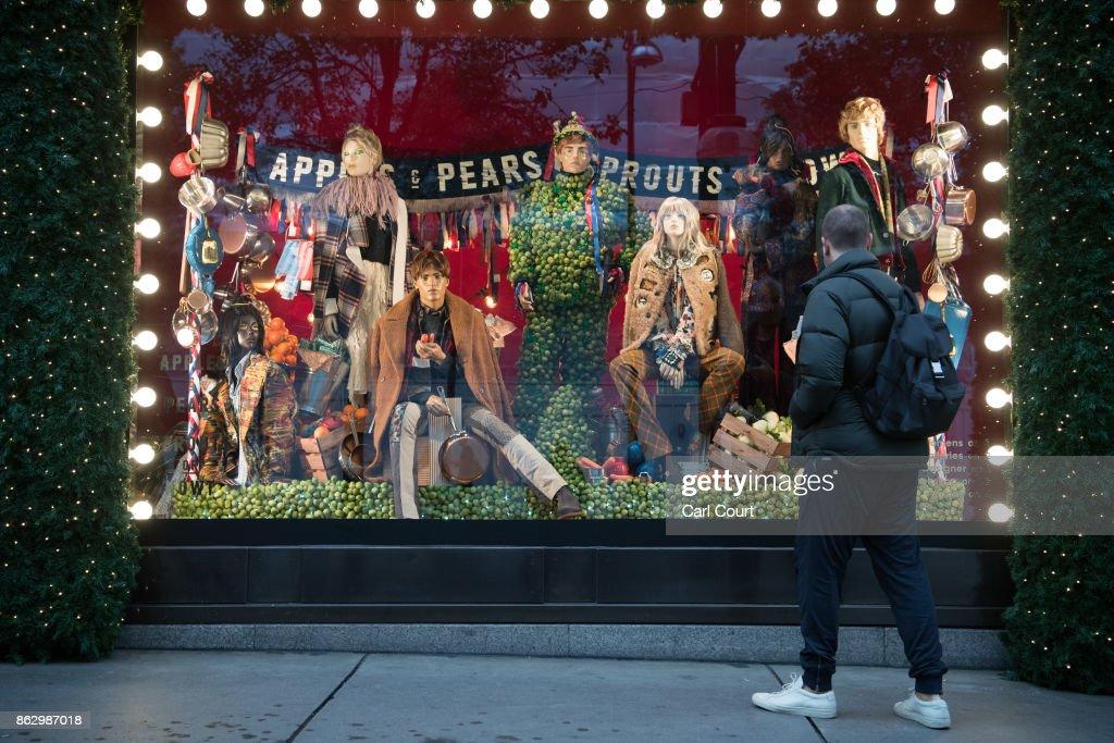 A woman views a Christmas window display at Selfridges on