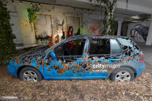 A woman views a derelict car installation by Dan Rawlings at the preview of Moniker Art Fair on October 04 taking place during Frieze Week at the Old...