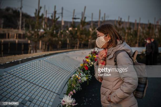 Woman views a newly-unveiled memorial bearing the names of the 3173 people who were killed during the 2011 Tohoku earthquake and tsunami on March 11,...