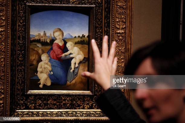 A woman views a painting by Raphael entitled 'Esterhazy Madonna' at the exhibition 'Treasures from Budapest' at the Royal Academy of Arts on...