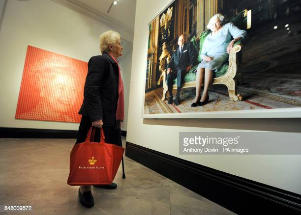A woman views a photograph titled Queen Elizabeth II and The Duke of Edinburgh Windsor Castle 2011 by Thomas Struth as Elizabeth Vs Diana by Kim...