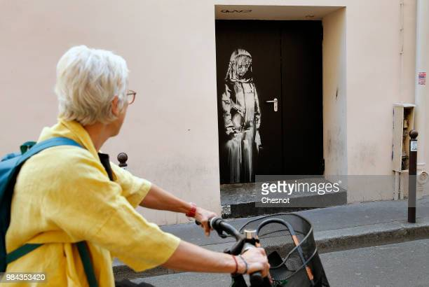 A woman views a recent artwork attributed to street artist Banksy on June 26 2018 in Paris France Yesterday a new artwork attributed to street artist...