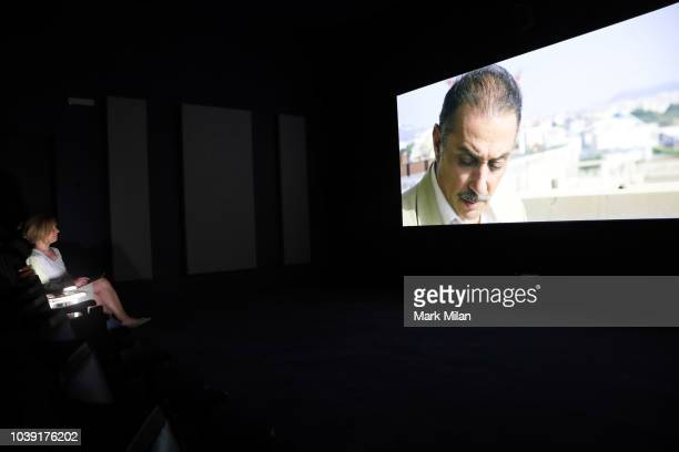 A woman views a video piece by artist Naeem Mohaiemen during the Turner Prize 2018 Photocall held at Tate Britian on September 24 2018 in London...