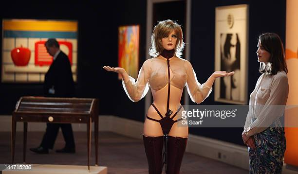 A woman views an Allen Jones hatstand in the shape of a scantilyclad woman in Sotheby's auction house which is expected to fetch 40000 GBP on May 18...