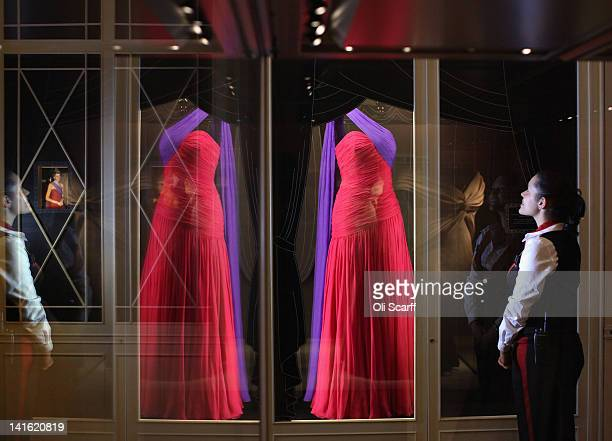 A woman views an evening dress designed by Catherine Walker and worn by Princess Diana on an official visit to Thailand in 1988 on display in...