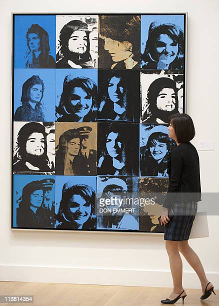 A woman views Andy Warhol's 'Sixteen Jackies' at Sotheby's May 6 2011 in New York The piece is featured in Sotheby's May 10 2011 Contemporary Art...