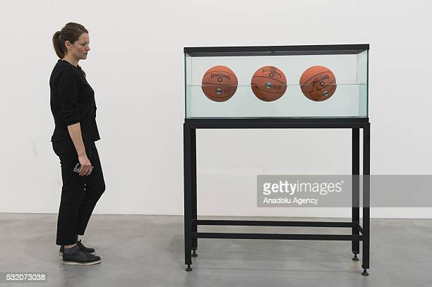 A woman views artwork titled Three Ball 50/50 Tank by artist Jeff Koons on display as part of the Jeff Koons Now art exhibition showing at the...