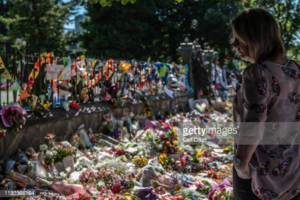 A woman views flowers and tributes by the wall of the botanic gardens on March 24 2019 in Christchurch New Zealand 50 people were killed and dozens...