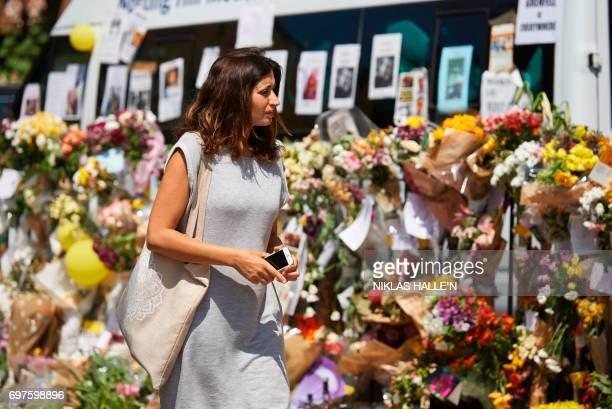 A woman views flowers left as a tribute to the victims and the missing from the Grenfell Tower block fire outside Notting Hill Methodist Church close...