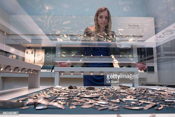 A woman views historic artifacts on display from the 'Cuerdale Hoard' in the new gallery 'Sutton Hoo and Europe AD 3001100' in the British Museum on...
