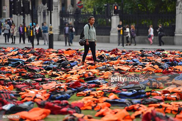 A woman views lifejackets that have been used by refugees to cross the sea to Europe as they are laid out in Parliament Square on September 19 2016...