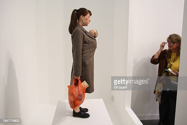A woman views Ron Mueck's artwork 'Woman with Shopping' at the Frieze London art fair on October 16 2013 in London England The annual Frieze Art Fair...