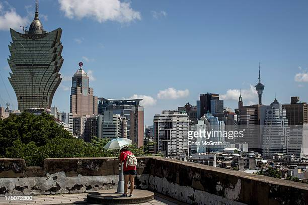 Woman views the Grand Lisboa Hotel and Casino from the Monte Fort on July 29, 2013 in Macau, Macau. Macau, the only place in China with legalized...