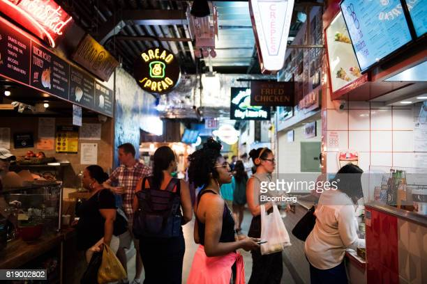 A woman views the menu of a food stand inside DeKalb Market Hall at City Point in the Brooklyn borough of New York US on Tuesday July 18 2017...