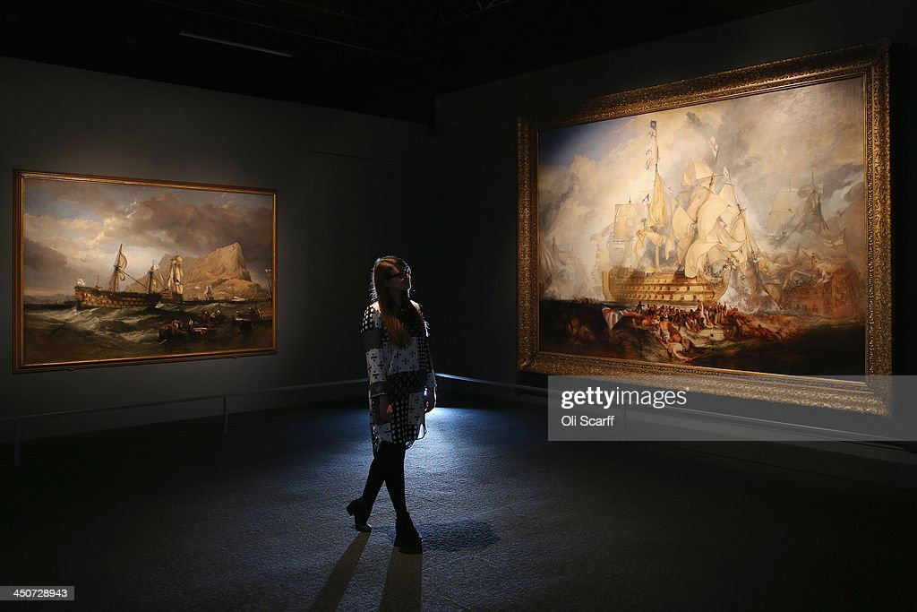A woman views the painting 'The Battle of Trafalgar' (R) by J.M.W. Turner in the exhibition 'Turner & the Sea' at the National Maritime Museum on November 20, 2013 in Greenwich, England. The exhibition, which opens on November 22, 2013 and runs until April 21, 2014, brings together 120 works of art by the great British painter of the sea.