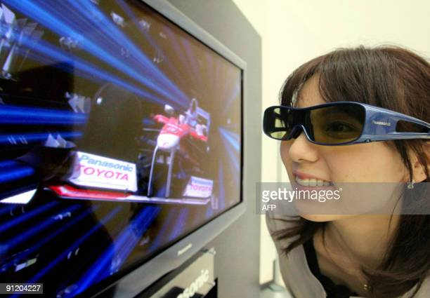 A woman views threedimensional images through special glasses on one of Japanese electronics giant Panasonic's new 50inch plasma display panel...
