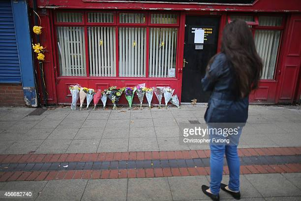 A woman views yellow ribbons and bouquets of flowers are outside the minicab office where murdered aid worker Alan Henning worked on October 5 2014...