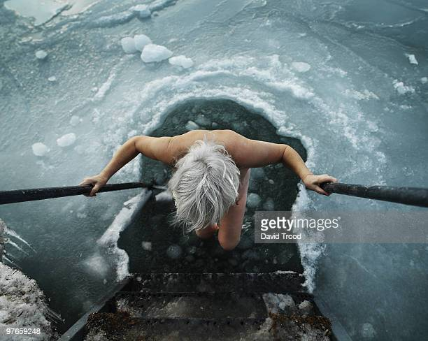 Woman viking going into hole in the ice.