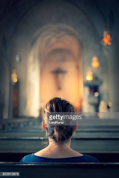 woman visiting a christian church - katholicisme stockfoto's en -beelden