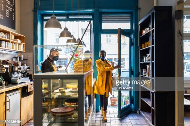 woman visiting a small coffee shop during pandemic - coat stock pictures, royalty-free photos & images