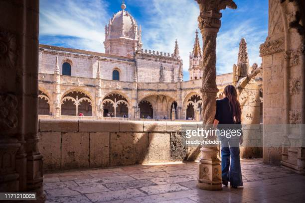 woman visiting cloisters of jeronimos monastery in lisbon, portugal - cloister stock pictures, royalty-free photos & images