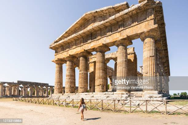 woman visiting the old ruins of paestum, italy. - archeologia foto e immagini stock