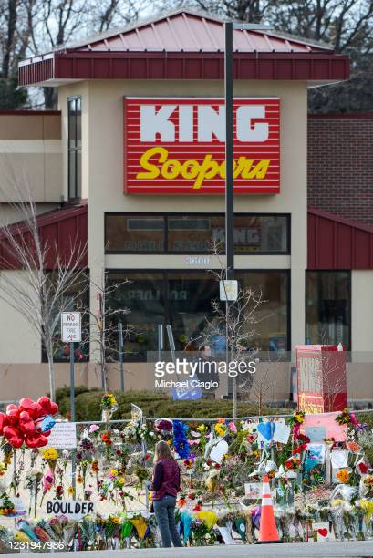 Woman visits a makeshift memorial outside a King Soopers grocery store on March 26, 2021 in Boulder, Colorado. Ten people, including a police...