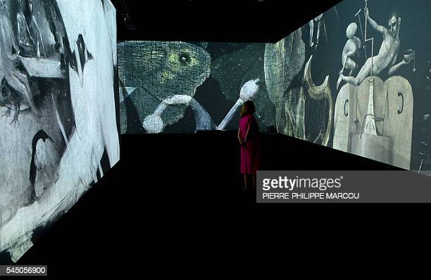 A woman visits a video installation on Dutch painter Hieronymus Bosch's masterpiece The Garden of Earthly Delights at El Prado museum in Madrid on...