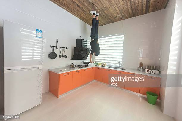 A woman visits in the villa standing upside down at Yantou village on June 14 2016 in Ningbo Zhejiang Province of China The upsidedown villa covered...