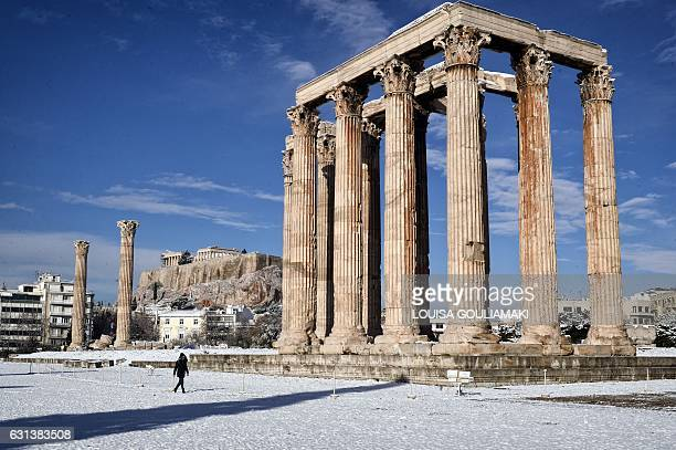 TOPSHOT A woman visits the archaeological site of Olympion Zeus in Athens after a rare heavy snowfall on the city on January 10 2017 A cold snap...