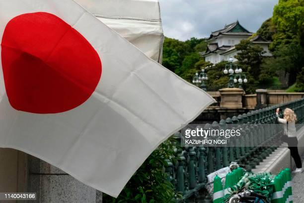 A woman visits the outer garden of the Imperial Palace in Tokyo on April 29 2019 Japan's Emperor Akihito will step down from the Chrysanthemum Throne...