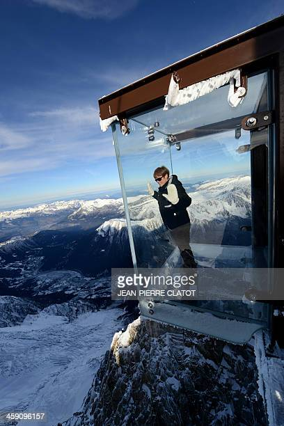 A woman visits the 'Step into the Void' glass skywalk overlooking the French Alps on top of a 3842metre peak in Chamonix on December 23 2013 The...