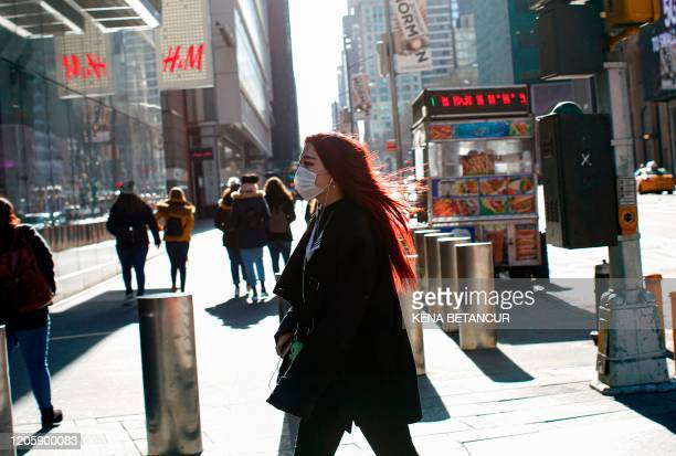 Woman visits Times Square as she wears a face mask on March 8, 2020 in New York City. - The governor of New York on March 7, 2020 announced a state...