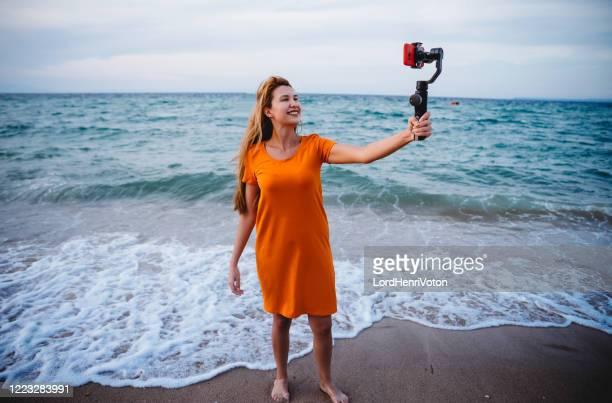 frau vlogging vom meer - reporterstil stock-fotos und bilder