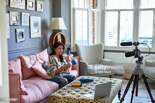 woman vlogging with camcorder showing various drinks bottles - one mid adult woman only stock pictures, royalty-free photos & images