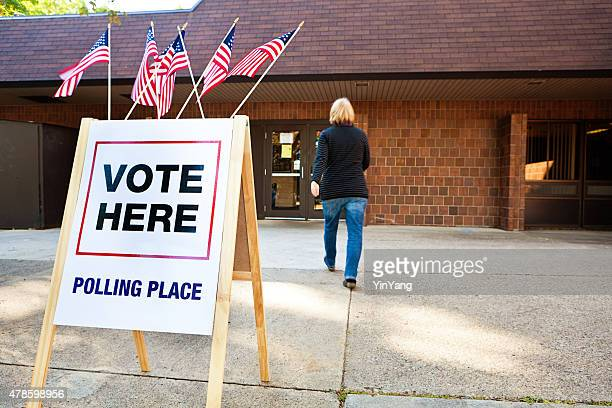 woman voter entering voting polling place for usa government election - election stock pictures, royalty-free photos & images