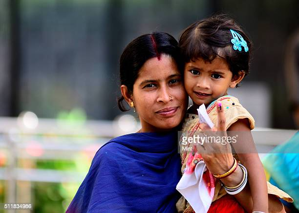 A woman voter holding her kid shows the mark after casting her vote for general election of the 16th Lok Sabha 2014 on April 10 2014 in New Delhi...