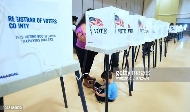 A woman votes from a booth as her child plays with a cellphone below inside the gymnasium at the Barack Obama Prep Academy on November 6 2018 in Los...
