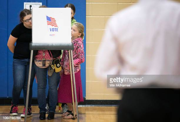 A woman votes with her with her three daughters at Deep Run High School November 6 2018 in Glen Allen Virginia The US holds its midterm elections...