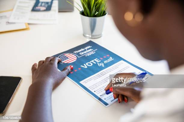 woman voting from home for the usa election - voting by mail stock pictures, royalty-free photos & images