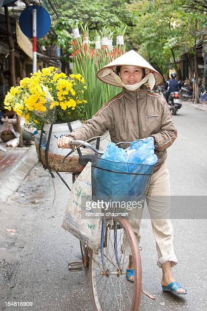 woman w conical hat selling flowers from bicycle