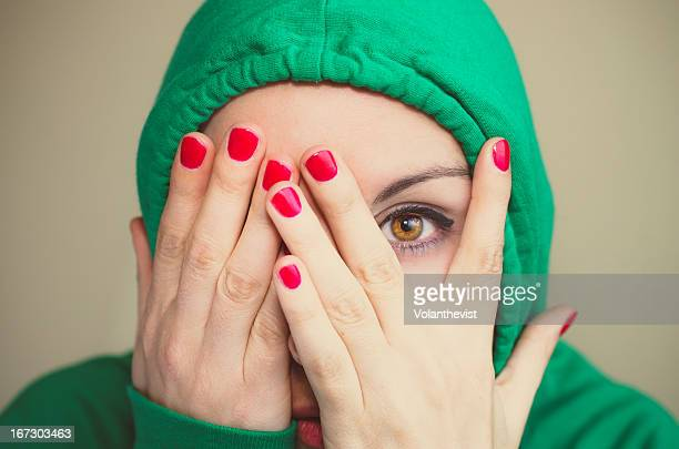 Woman w/ green hood looking through the fingers