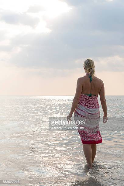 Woman wades into shallows, looks out to sea