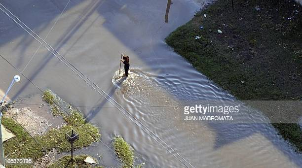 A woman wades through a flooded road in the outskirts of La Plata Argentina on April 3 2013 Massive flooding killed 54 people in and around Buenos...