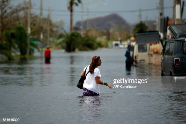 A woman wades through a flooded street in the aftermath of Hurricane Maria in San Juan Puerto Rico on September 22 2017 Puerto Rico battled dangerous...