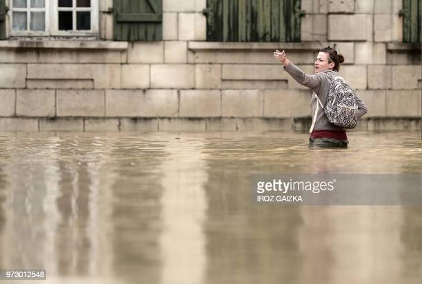 A woman wades through flood waters sweep through the streets following heavy rains in SaliesdeBearn south western France on June 13 2018