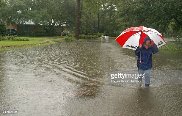 A woman wades through her flooded neighborhood as heavy rains from Tropical Storm Ernesto continue to fall August 31 2006 in Wilmington North...