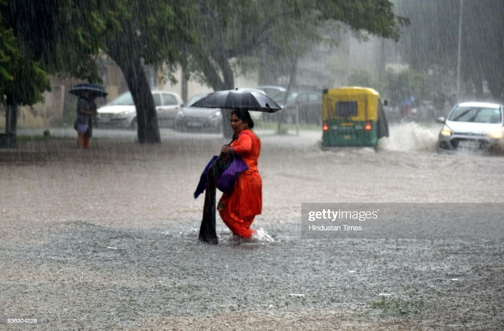 A woman wades through knee deep water as it rains heavily at sector 41 on August 21 2017 in Chandigarh India Heavy rainfall on morning brought the...